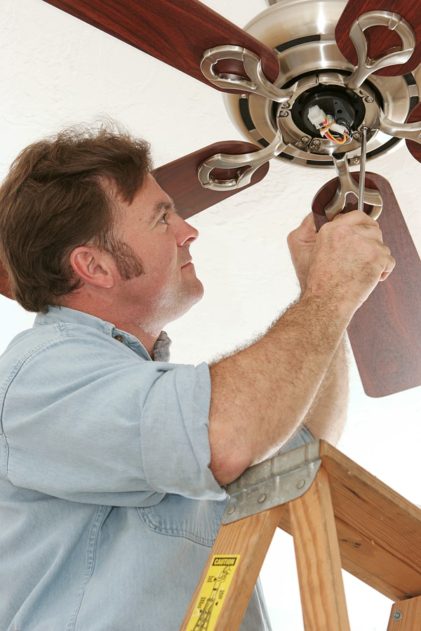 Service tech working on ceiling fan